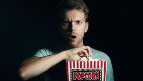 Portrait Of Surprised Man Eating Popcorn Against Black Background