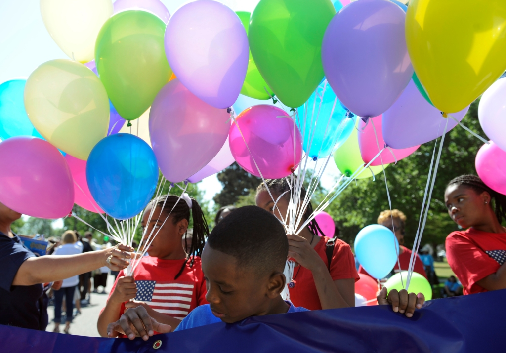 Brian Harris, 8, waits for the parade to begin with his mom and other employees from US Bank. The Friends of Blair Caldwell African American Research Library Foundation hosts the 2011 Denver Juneteenth Celebration: We Define Who We Are, on Saturday, June