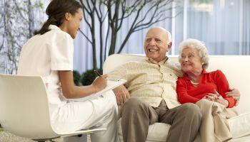Nurse attending an elderly patient couple
