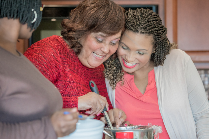 Senior mother smiles while cooking with her adult daughters in kitchen