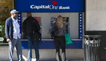 People use an ATM at a Capital One Bank
