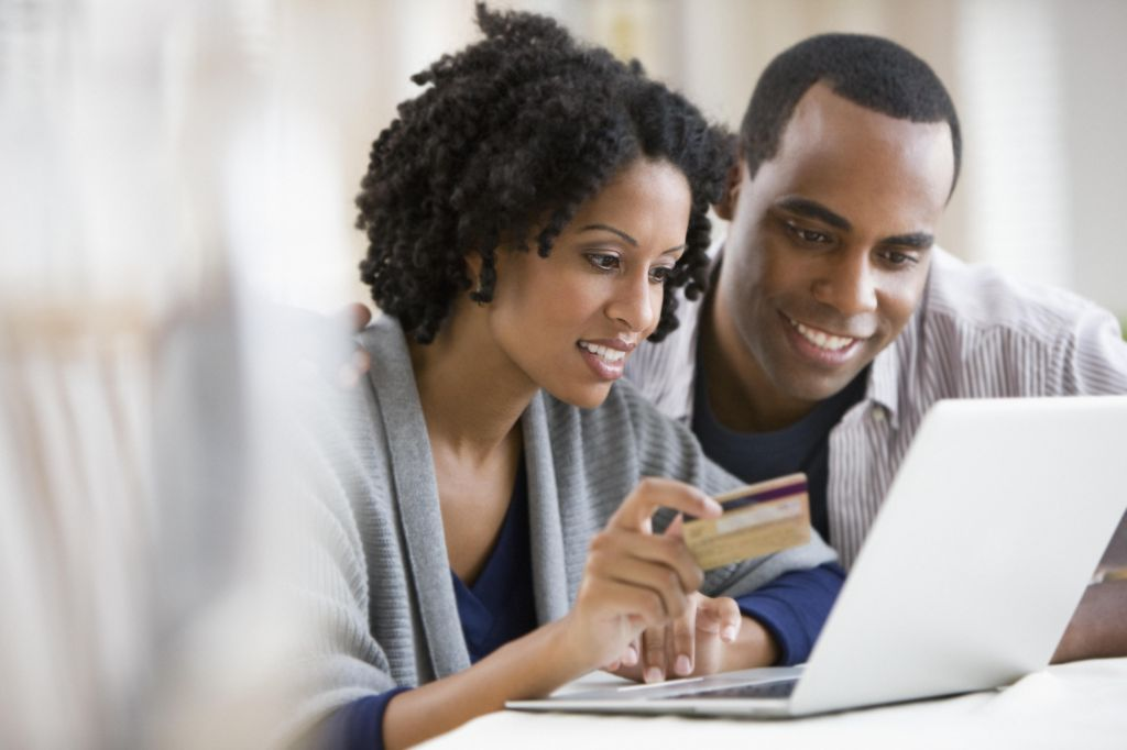 Couple holding credit card and using laptop