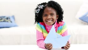 Smiling little girl at home with a paper boat